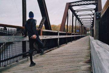 Man stretching leg on bridge running in winter