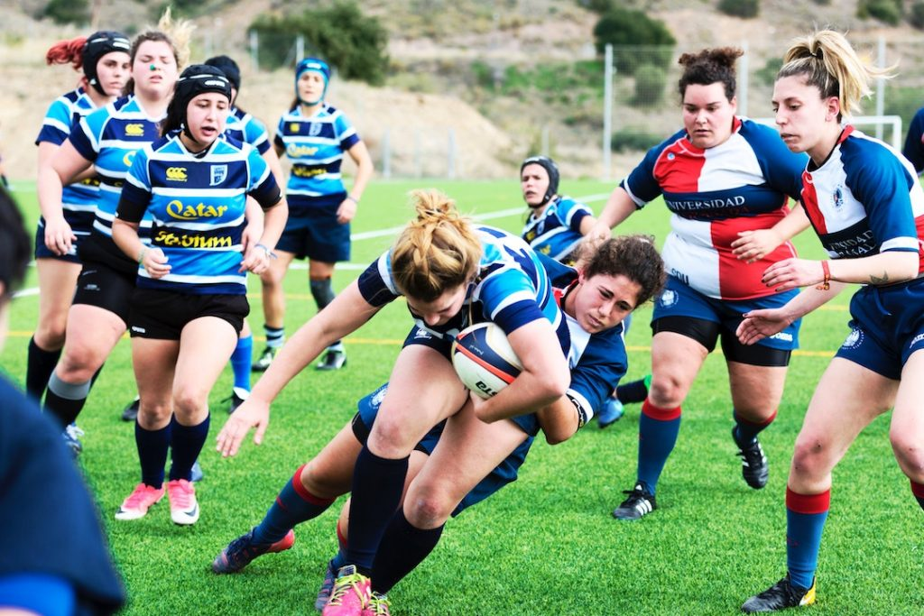 Women playing rugby.